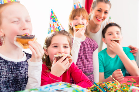 children birthday: Children grabbing muffins at birthday party and cake, the kids are wearing hats, balloons and paper streamers for decoration Stock Photo