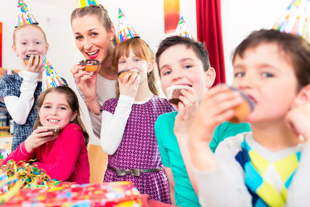 children birthday: Children having cupcakes celebrating birthday on big party with all the friends and mom Stock Photo