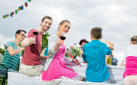 family and friends: Couple toasting with wine at garden party with friends and family Stock Photo