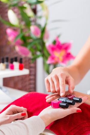 salon beaut�: Femme choisissant vernis � ongles dans un salon de beaut� pour recevoir une manucure