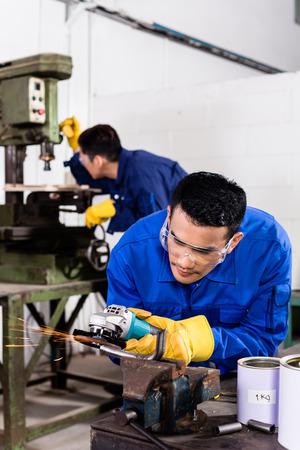 industriales: Dos trabajadores de la industria de Asia en la f�brica de metal con herramienta de molienda el�ctrica y la m�quina taladradora