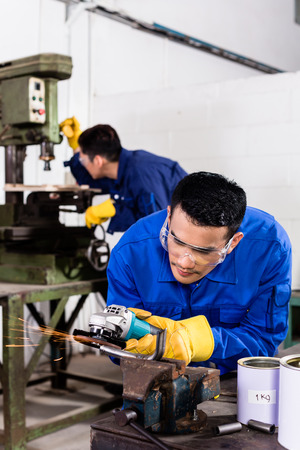 Industrial workers: Two Asian industrial workers in metal factory with electrical grinding tool and power drill machine