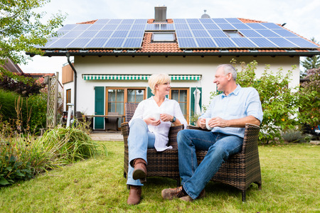 energia solar: Pareja de hombre y mujer que se sienta delante de su hogar o casa en sillas de mimbre