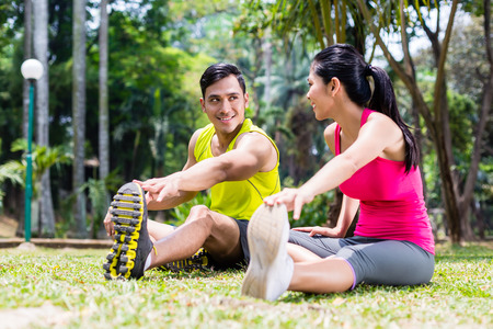 asian sport: Asian woman and man, a couple, during gymnastics stretching for sport fitness in tropical park