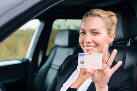 Donna mostrando la sua patente di guida dalla finestra di automobile Archivio Fotografico