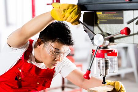 empleados trabajando: Hombre chino que trabaja con la m�quina de perforaci�n poder en la f�brica