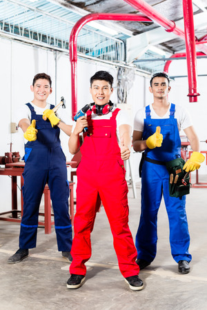 work tools: Three Asian industrial workers, a manufacturing team, standing proud in factory giving the thumbs up sign