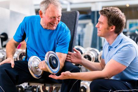 aide à la personne: Senior homme et formateur à l'exercice dans le gymnase avec des poids haltères