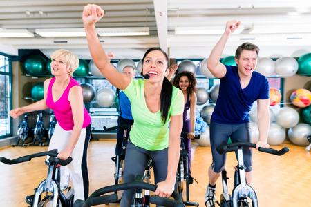 curso de capacitacion: Grupo de hombres y mujeres que hacen girar en las bicicletas de fitness en el gimnasio, la gente la diversidad, viejos, j�venes, blanco y negro Foto de archivo