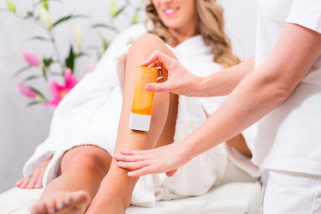 depilation: Woman receiving waxing for hair removal in beauty parlor