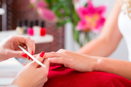 close shot: Woman getting manicure in nail parlor with file, close shot