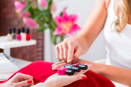 Woman choosing nail polish in beauty parlor to receive a manicure photo