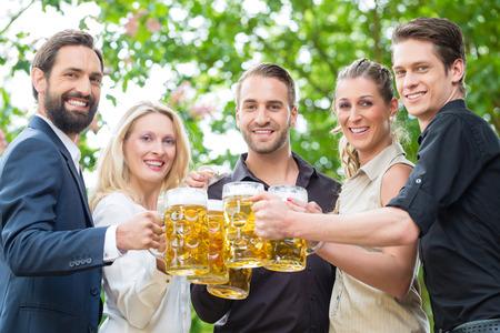 after to work: Compa�eros de trabajo despu�s de la reuni�n de trabajo en beergarden beber un vaso de cerveza fresca, tuestan al espectador