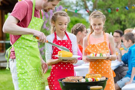 parrillada: Familia que tiene barbacoa en la fiesta de jardín, papá está poniendo maíz y verduras a la parrilla en las placas de hijas Foto de archivo