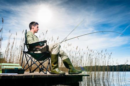 hombre pescando: El hombre pesca en el lago que se sienta en el embarcadero cerca del agua