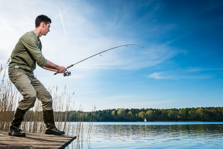un p�cheur: P�cheur attraper la p�che de poissons au bord du lac sous un ciel bleu Banque d'images