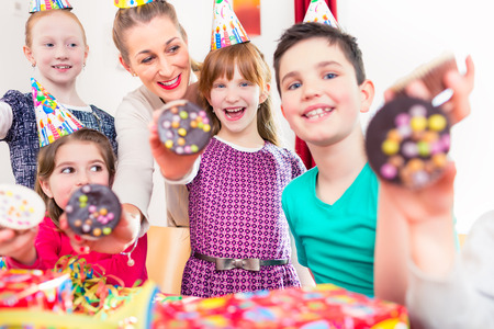 child birthday: Kids showing muffin cakes into the camera at birthday party, larger group of children and mother