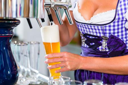 wheat beer: Innkeeper in Bavarian pub drawing beer