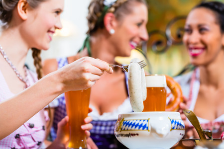 german: White veal sausage breakfast in Bavaria, three girls eating and drinking Stock Photo