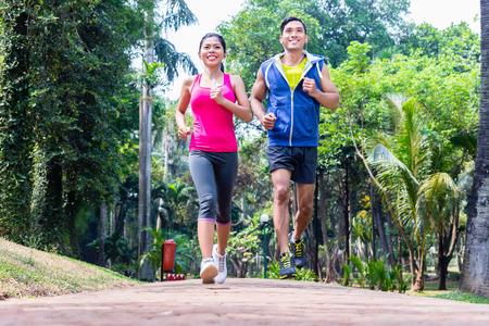 corriendo: Asia pareja, hombre y mujer, trotar o correr en el parque tropical de Asia para la aptitud