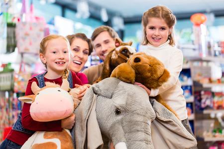 juguetes: Familia con elefante de peluche en la tienda de juego juguete, muchacha que se sienta en el juguete de felpa
