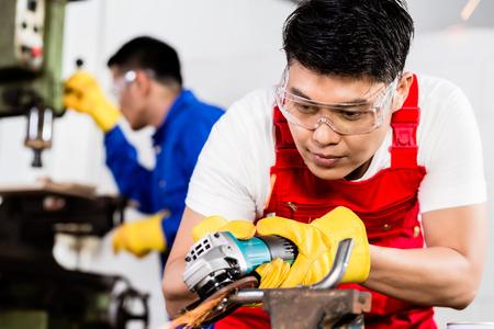 diligente: Dos trabajadores de la industria en la fábrica de metal de Asia con la herramienta abrasiva y la máquina eléctrica taladro eléctrico Foto de archivo