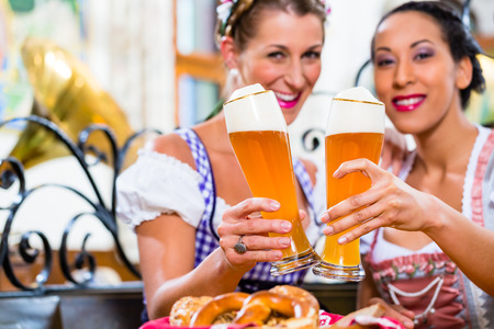 tracht: Women in Bavarian pub wearing traditional Tracht toasting with wheat beer Stock Photo