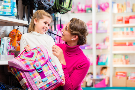 satchel: Mother and kid becoming a student buying school satchel or bag in store
