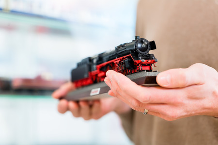 railroads: man buying model railroad in toy store holding the model in his hands, close-up