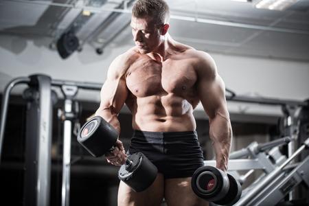 fortaleza: Bodybuilder en gimnasia en el entrenamiento de fitness con pesas de pie delante de equipos