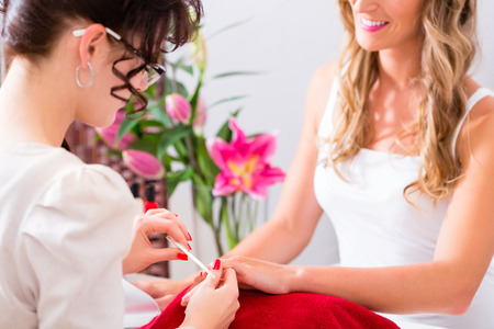 parlor: Woman getting manicure in nail parlor with file