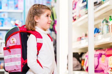 niño escuela: Niña elegir suministros para primer día en la escuela