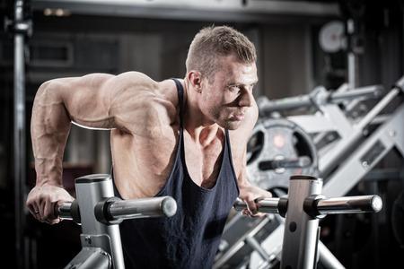 Bodybuilder man in sportschool doen dips als arm training