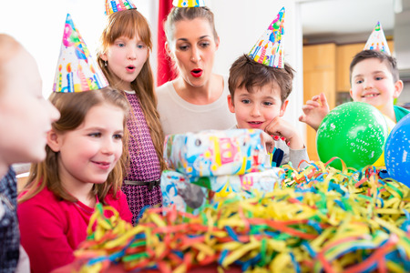 birthday presents: Child unwrapping birthday gift with friends at home birthday party, mom is helping