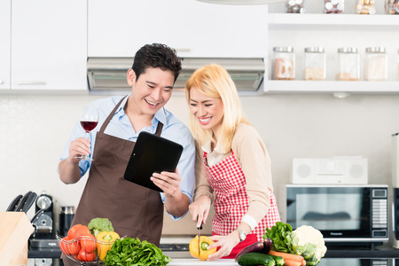 clean food: Asian couple cooking after recipes from tablet computer