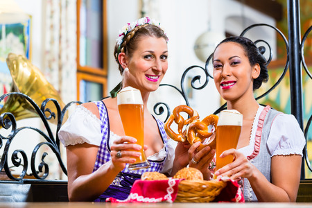 Girlfriends with Pretzel and Beer in Bavarian Inn eating and drinking Stock Photo