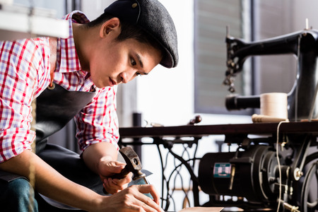 saddler: Asian shoe or belt maker in his leather workshop with sawing machine  Stock Photo