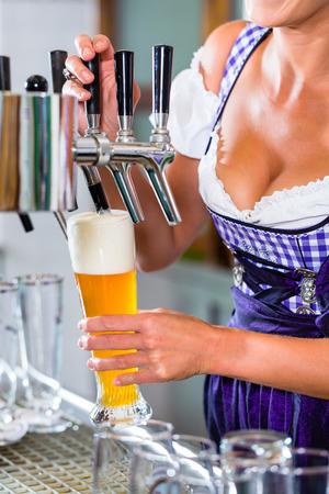 tracht: Innkeeper in Bavarian pub drawing beer