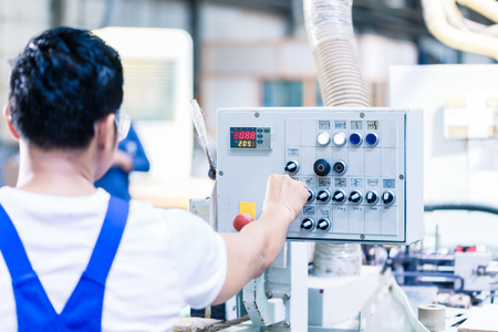 cnc: Worker pressing buttons on CNC machine control board in Asian factory Stock Photo