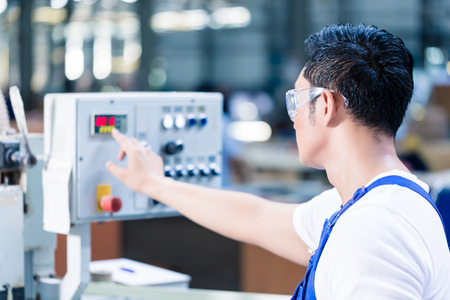 Worker pressing buttons on CNC machine control board in Asian factory Stock Photo
