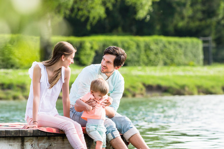 children pond: Happy family sitting on jetty on lake or pond letting feet hang into the water