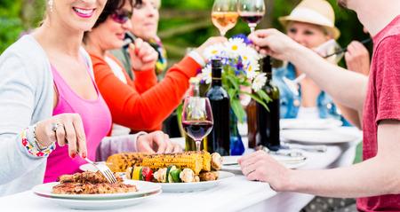 Vrouwen en mannen vieren tuinfeest, eten en drinken samen