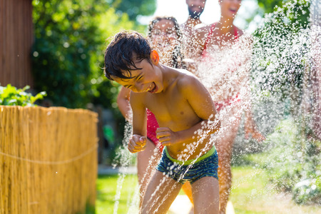 heat wave: Family cooling down with sprinkler in garden, lots of water splashing around Stock Photo