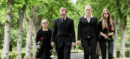 grave: Family on cemetery walking down alley at graveyard with roses
