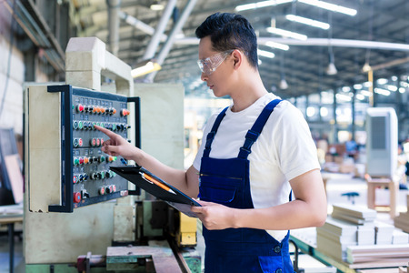Worker pressing buttons on CNC machine control board in Asian factory Foto de archivo