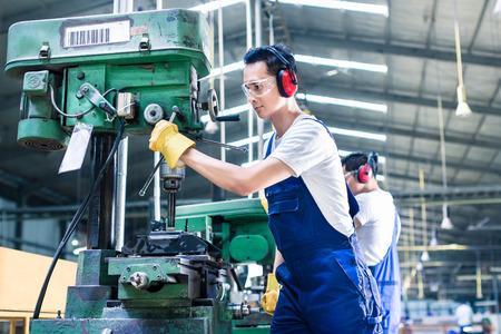 obrero: Asiatico trabajador en la planta de producción de la perforación en la máquina en la fábrica