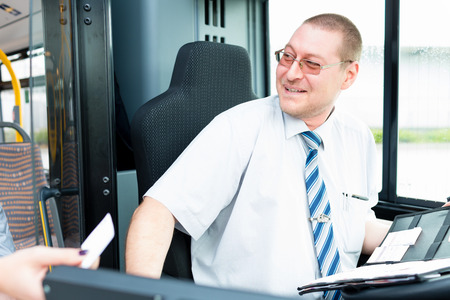 Bus driver selling tickets in bus from drivers seat