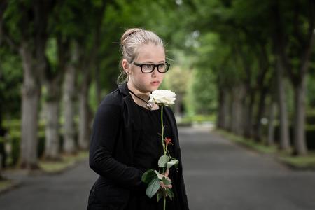 今孤児にされて墓地に故人を追悼白いバラを持つ少女 写真素材