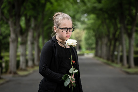 orphan: Girl with white rose mourning deceased on graveyard being an orphan now