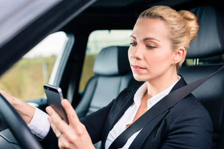 inattentive: Woman texting while driving angrily her car, looking in rage on his phone instead of traffic Stock Photo